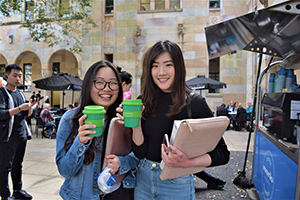 Students holding Green Caffeen cups