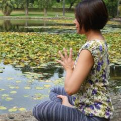 Lady meditating by the lake