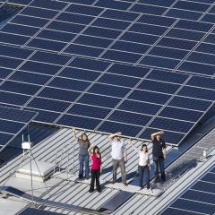 Rooftop solar panels with students waving