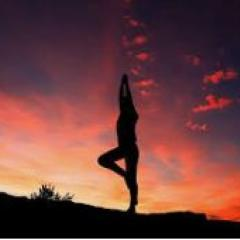 Yoga pose against orange sky at sunset