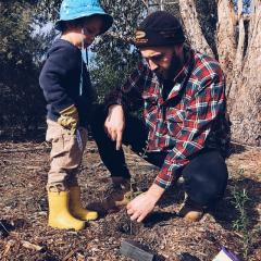 Father planting tree with son
